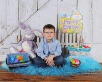 Stattlicher junger Junge, der in der Ostern-Szene sitzt Stockfoto