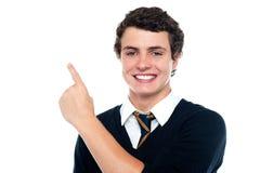 Stattlicher junger Junge in der Uniform, die aufwärts anzeigt lizenzfreie stockfotografie