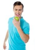 Stattlicher junger Kaukasier, der einen Apfel beißt stockbilder