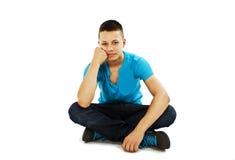Stattlicher junger Mann, der auf dem Fußboden sitzt Stockfotos