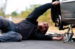 Stattlicher junger Mann, der Auto repariert Stockfotos