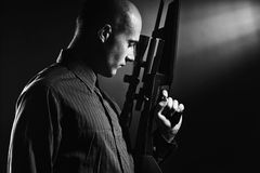 Stattlicher junger Mann, der eine Gewehr anhält. Lizenzfreies Stockfoto