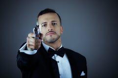 Stattlicher junger Mann, der eine Gewehr anhält Lizenzfreies Stockbild