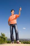 Stattlicher junger Mann, der eine Handyabbildung sendet Stockfoto