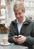 Stattlicher junger Mann, der eine Meldung texting ist Stockfotos