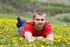 Stattlicher junger Mann, der in eine Wiese legt Lizenzfreies Stockfoto