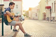Stattlicher junger Mann, der Gitarre spielt Stockbild