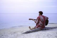 Stattlicher junger Mann, der Gitarre spielt Lizenzfreies Stockbild