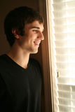 Stattlicher junger Mann, der heraus Fenster schaut stockbild