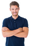 Stattlicher junger Mann, der mit den Armen gekreuzt lächelt Lizenzfreie Stockfotografie