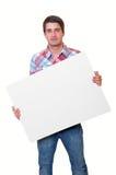 Stattlicher junger Mann, der unbelegte weiße Karte anhält lizenzfreie stockfotografie