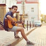 Stattlicher junger Mann mit Gitarre Stockbilder