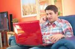 Stattlicher junger Mann mit Laptop unter Verwendung seines Telefons stockfotografie