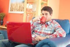 Stattlicher junger Mann mit trinkendem Kaffee des Laptops lizenzfreies stockfoto
