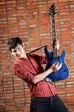 Stattlicher junger Musiker, der die Gitarre spielt stockfotos