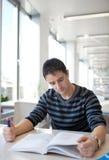 Stattlicher junger Student in einer Bibliothek Lizenzfreies Stockfoto