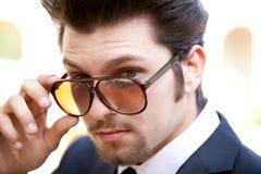 Stattlicher Kerl, der über Sonnenbrillen schaut Lizenzfreie Stockfotografie