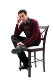 Stattlicher Kerl, der auf Stuhl sitzt stockfotografie