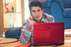 Stattlicher Kerl, der den Laptop und Telefon liegen auf Fußboden verwendet stockfotografie