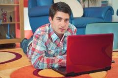 Stattlicher Kerl, der Laptop beim Lügen auf einem Fußboden verwendet lizenzfreies stockfoto