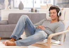 Stattlicher Kerl, der Musik auf Kopfhörern genießt Stockfotos