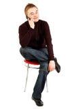 Stattlicher Kerl spricht durch bewegliches Sitzen auf einem Stuhl Lizenzfreie Stockfotografie