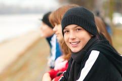Stattlicher lächelnder Jugendjunge draußen mit Freunden Stockbilder