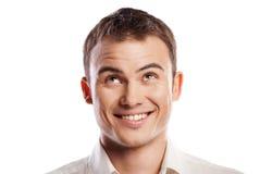 Stattlicher lächelnder junger Mann, der oben getrennt schaut Lizenzfreie Stockfotos