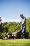 Stattlicher mähender Rasen des jungen Mannes Lizenzfreies Stockfoto