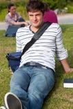 Stattlicher männlicher Kursteilnehmer, der auf Gras mit seinem Beutel liegt Stockbild