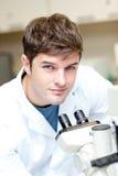 Stattlicher männlicher Wissenschaftler, der ein Mikroskop verwendet Stockfoto