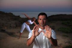 Stattlicher Mann auf dem Strand meditierend Stockbilder