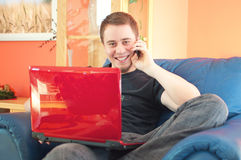 Stattlicher Mann, der auf Sofa mit Telefon und Laptop sitzt stockbild