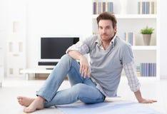 Stattlicher Mann, der auf Wohnzimmerfußboden sitzt Lizenzfreies Stockfoto