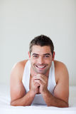 Stattlicher Mann, der beim Bettlächeln liegt Stockfoto
