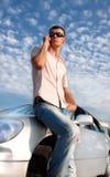 Stattlicher Mann, der durch Mobiltelefon nahe Auto benennt Lizenzfreie Stockbilder