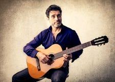 Stattlicher Mann, der Gitarre spielt Stockfoto