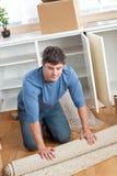 Stattlicher Mann, der heraus einen Teppich rollt Stockfotografie
