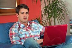 Stattlicher Mann, der an Laptop in einem Wohnzimmer arbeitet lizenzfreie stockbilder
