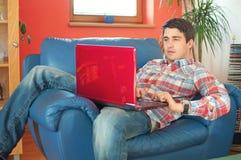 Stattlicher Mann, der an Laptop im Wohnzimmer arbeitet stockfotos
