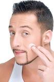 Stattlicher Mann, der männliche Creme auf Gesicht anwendet Lizenzfreies Stockbild
