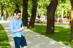 Stattlicher Mann, der smartphone hörende Musik betrachtet Stockfotografie