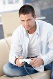 Stattlicher Mann, der zu Hause das lächelnde Videospiel spielt Lizenzfreie Stockfotos