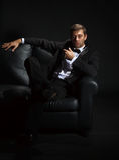 Stattlicher Mann in einem Smoking auf Couch Stockfotografie