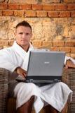 Stattlicher Mann im Bademantel mit Computer Stockfotografie