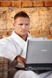 Stattlicher Mann mit Computer im Bademantel Stockfotos