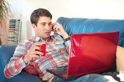 Stattlicher Mann mit Kaffee und Laptop auf dem Sofa lizenzfreie stockfotografie