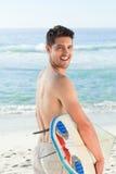 Stattlicher Mann neben dem Meer mit seinem Surfbrett Stockbild