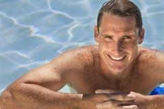 Stattlicher mittlerer gealterter Mann, der im Swimmingpool sich entspannt Lizenzfreie Stockfotografie