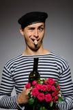 Stattlicher romantischer Mann mit rosafarbener Blume und Rebe Lizenzfreies Stockbild